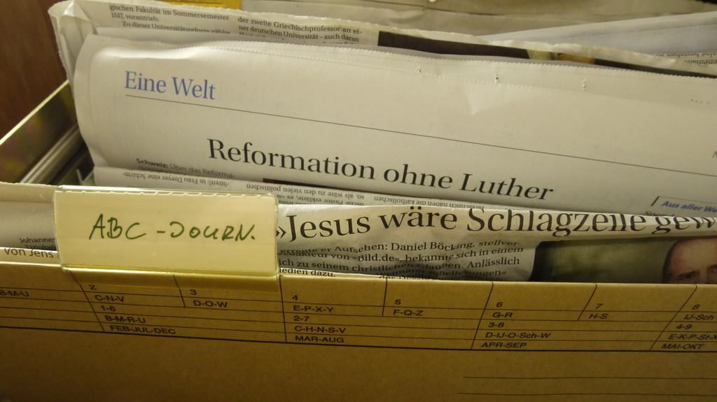 Hängeregistratur mit Zeitungsausschnitten. Beschirtung ABC-Journal. SIchtbare Überschriften auf Zeitungen: Reformation ohne Luther, Jesus wäre Schlagzeile