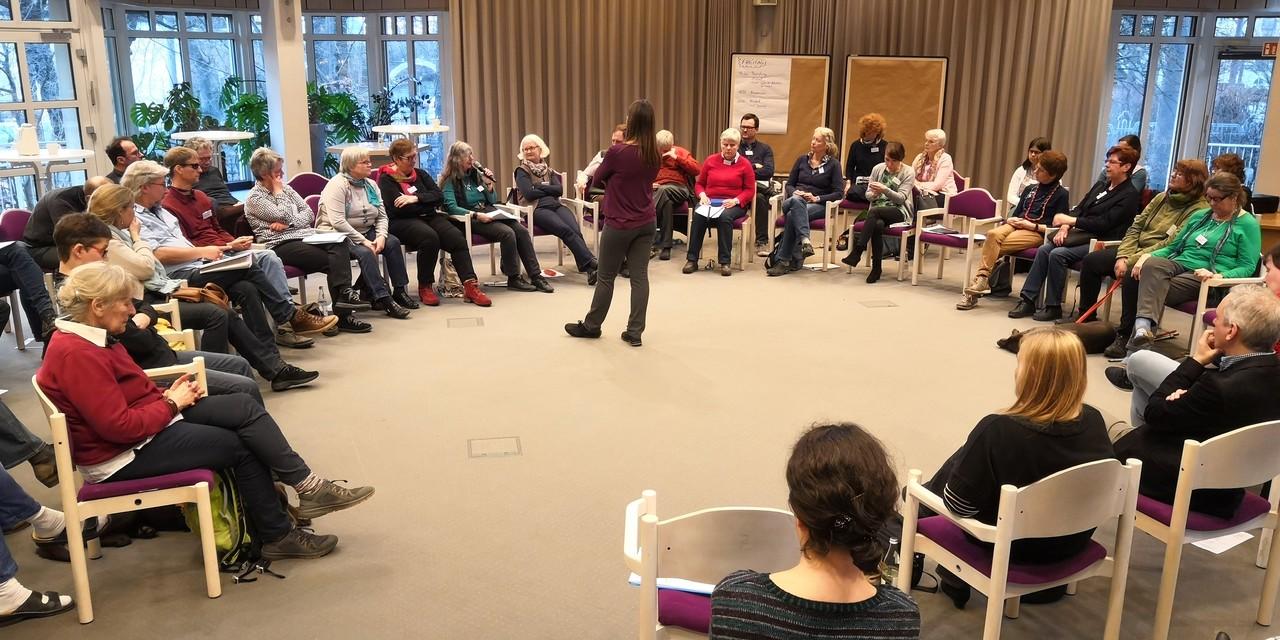 Teilnehmer des DeBeSS Fachtag sitzen im Kreis, in der Mitte Referentin Pfr. B. Brusius