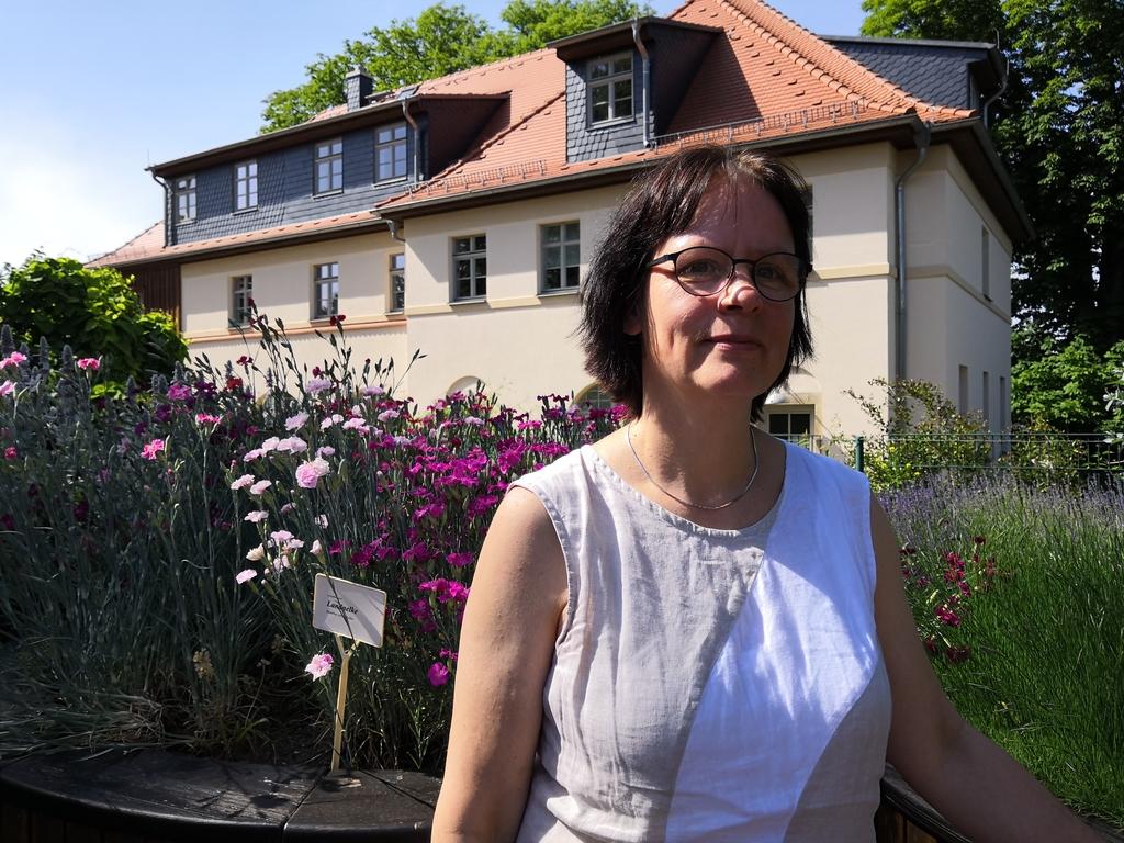 """Pastorin Fourestier im Duftgarten, links bunte Blumen, im Hintergrund das Haus """"Storchennest"""""""