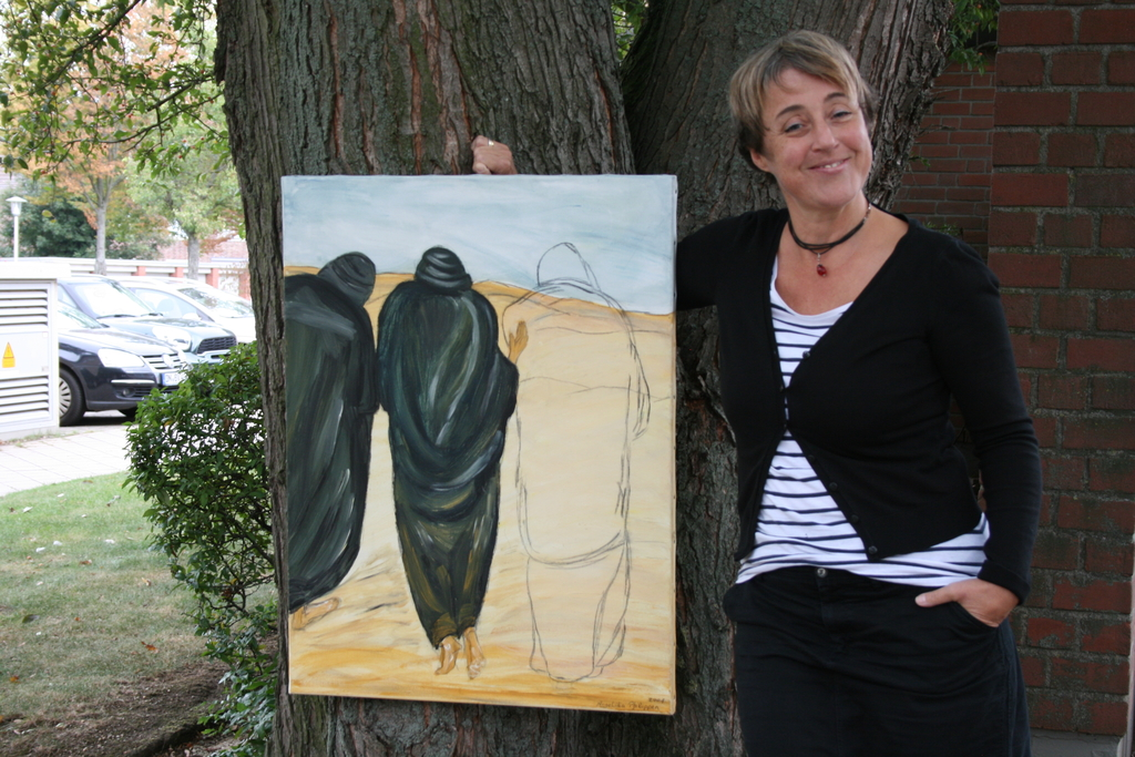 Jutta Busch steht unter einem alten Baum neben einem Gemälde auf dem die Emmausjünger abgebildet sind