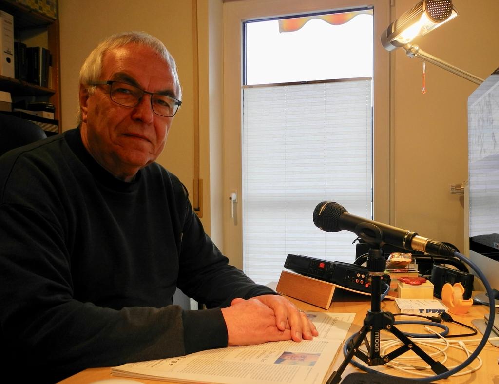 Norbert Obst am Schreibtisch mit Aufnahmegerät und Mikrofon