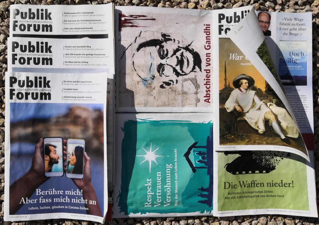 Viele Ausgaben von Publik Forum liegen auf einem Platz am Boden, die Titelthemen sind zu erkennen. eine Ausgabe wird durch den Wind gerade aufgeblättert