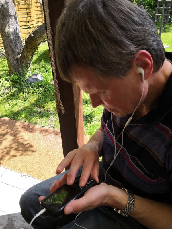 Der blinde Pfarrer Mario Buchmann tastet auf seinem Handy, im Ohr die Ohrhörer
