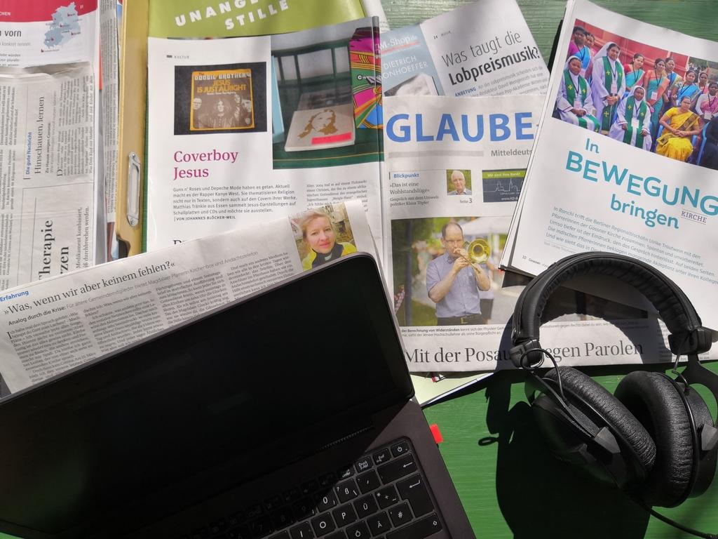 Zeitungen und Zeitschriften, ein Laptop und ein Kopfhörer auf einem Tisch