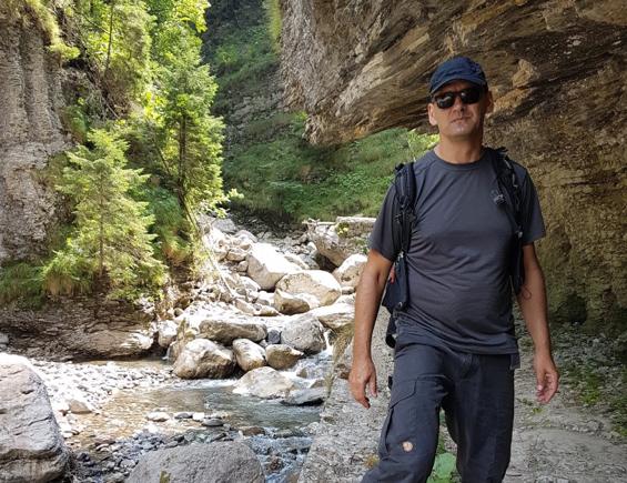 Mario Krenitz wandernd in den Bergen neben einem Felsen