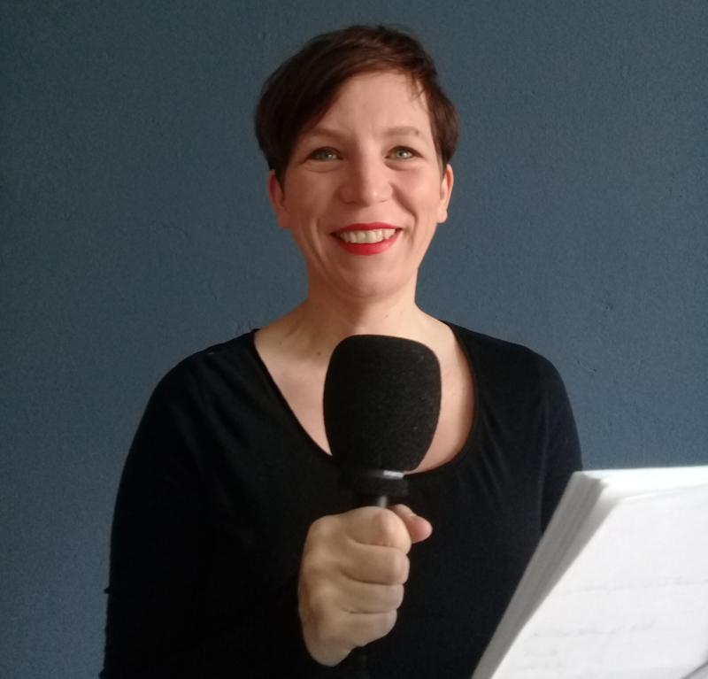 Anna schönberg mit dem Mikro in der Hand an einem Lesepult stehend