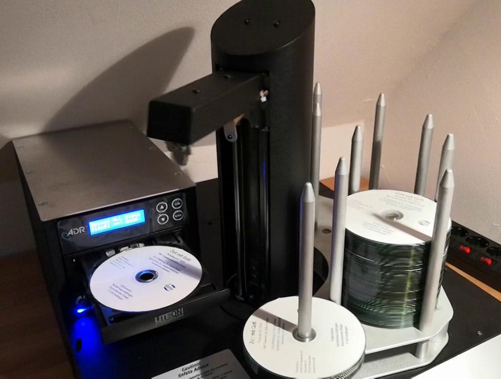 Ein CD-Kopierroboter nimmt mit einem Greifarm CDs vom Stapel, legt sie in den Brenner und entnimmt sie anschließend wieder