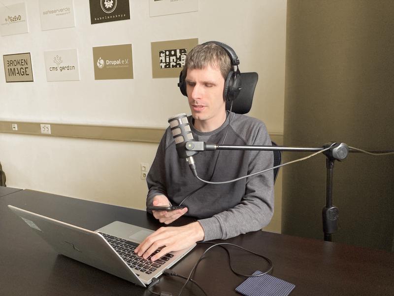 Dennis Westphal am Tisch vor einem Mikrofon mit Kopfhörer sitzend. In der Hand ein Phone, vor sich ein Laptop. An der Wand dahinter Logos der Geschäftsbereiche der Gesellschaft zur Entwicklung von Dingen, z.B. den Bereich Broken Image