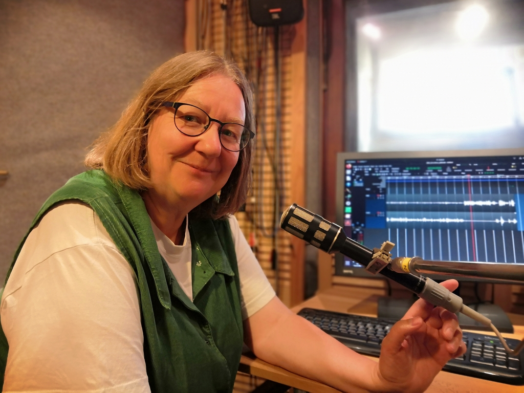 Dorothee Janssen schaut in die Kamera. Mit dem Finger zeigt sie zum Mikrofon. Im Hintergrund auf dem Bildschirm die OpenSource Audiobarbeitungssoftware Ardour